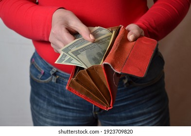 Hands of young woman in red blouse and jeans, holding an open  red purse with dollars and. Studio shot, close-up. - Shutterstock ID 1923709820