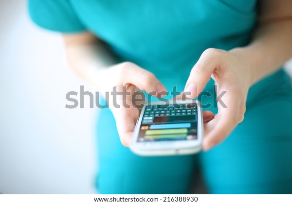Hands of young woman sending text message from smart phone at work