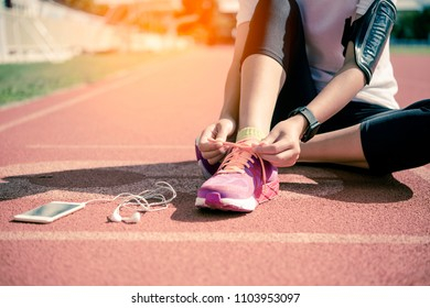 Hands of a young woman shoelace and pink sneakers on a jogging track in the morning to exercise