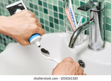 Hands of young woman squeezing black charcoal toothpaste from tube on a white toothbrush at bathroom. Colorful toothbrushes are visible in background. Whitening toothpaste. Dental health.