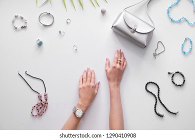 Hands of young woman and stylish bijouterie on white background
