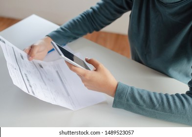 hands of young woman using mobile smart phone for scan and payment online with family budget cost bills on desk in home office, plan money cost saving, investment, business finance, expenses concept