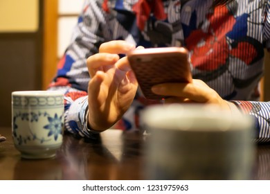 Hands of young woman using smartphone in traditional Japanese restaurant, with ceramic cup of Japanese roasted green tea in the foreground (This tea looks like Chinese oolong tea)
