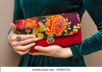 In the hands of a young woman wearing an elegant green velvet dress, a bright red clutch handbag with floral print on brown background. Women's day, fashion, spring, flower, rose, romance, love.
