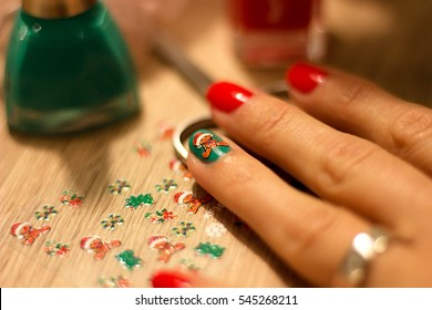 hands of a young woman who paints her nails red and green nail polish and decorate nails decorative sticker with a Christmas theme