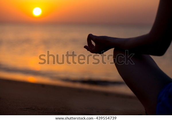 Hands of young woman in yogic mudra, doing yoga training on the beach, Sitting in Easy Pose, Sukhasana, meditating, relaxing at sunset or sunrise, back view, close up