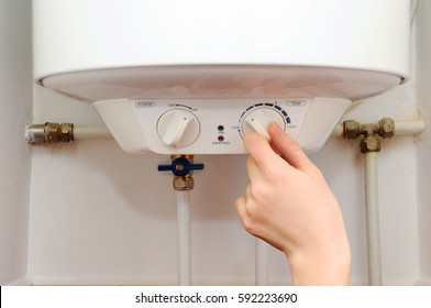 Hands young women set the temperature of the water in the electric boiler.