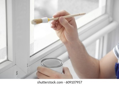 Hands of young worker painting window in office