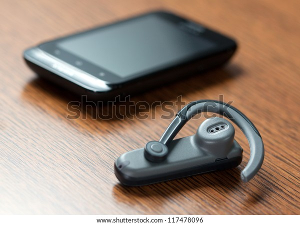 Handsfree with mobile phone in background