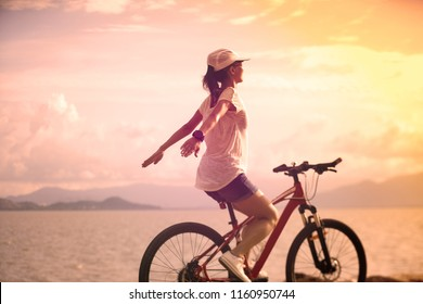 Handsfree woman riding a bike on sunny seaside with arms outstretched