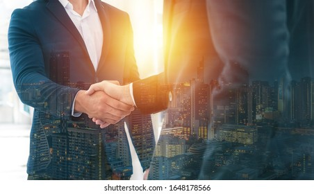 Handshake of 2 businessman in a black suit double exposure the business center city.mergers and acquisitions for start greeting with good etiquette negotiation the success of both