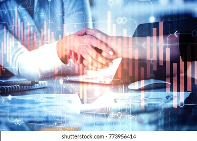 Handshake at abstract workplace with various items and abstract business chart projection. Teamwork and accounting concept. Double exposure