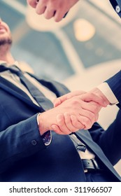 Handshake agreement. Two successful businessman standing in the restaurant and drink coffee while shaking hands with each other close-up view of hands
