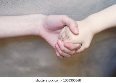 Handshake of baby boy and his older sister on blure grey brown wall background. Hold your arm to protect concept.