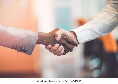 Handshake between african and a caucasian man