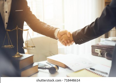 Handshake between attorneys and clients after agreeing to enter into a contract for a court case. In the hope of victory over legal fighters.