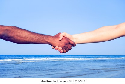 Handshake between black hand of african migrant and white american man on blue sky background - Current concept of policies on refugees reception humanitarian aid and world peace - Soft cyan filter