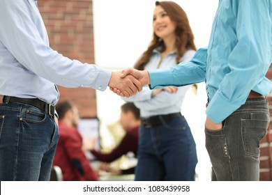Handshake between businesspeople in a modern office.