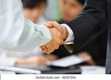 Handshake between employee and boss to illustrate he is being accepted in the team