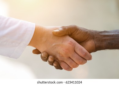 Handshake between female caucasian doctor's hand and black african man's hand.Unrecognizable people