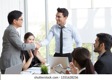 Handshake between the foreign CEO and the Asian manager who can successfully complete the project which makes the company gain profit from the annual sales top ranking in the region