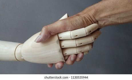 Handshake between human hand and wooden hand. Gray background. Horizontal
