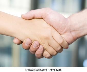 Handshake between office workers - man and woman