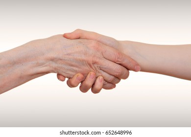 Handshake between an old person with a wrinkled hand and a kid.