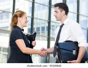 Handshake between two business workers outdoors. Communication between man and woman about business projects in front of business building.