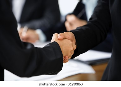 Handshake between two businesswoman with other business people on background. Different skin tones