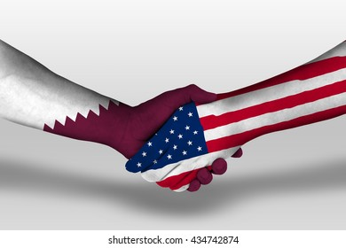 Handshake between united states of america and qatar flags painted on hands, illustration with clipping path.