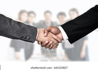 Handshake of business partners after signing contract with teamwork background