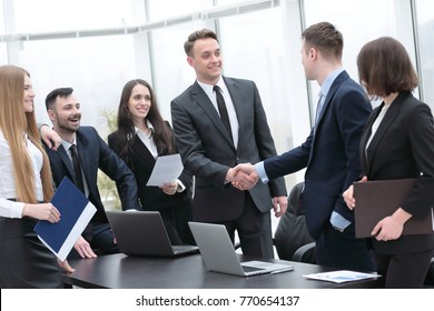 handshake business partners at a meeting in the office