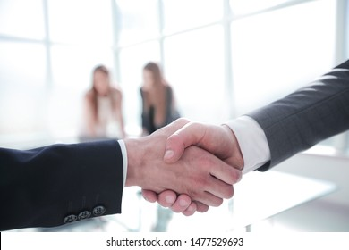 handshake of business partners on the background of the office
