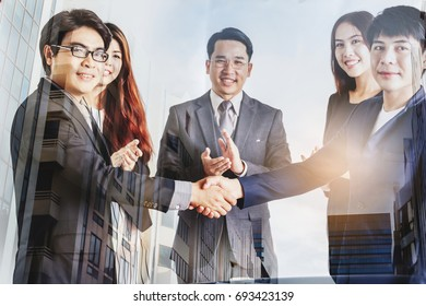 Handshake of business partners on blur office building background - Double exposure photo