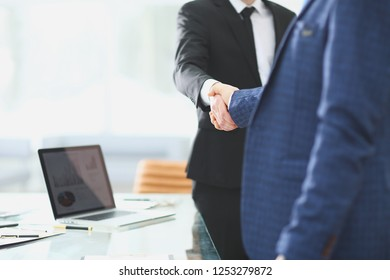 handshake business partners standing next to the Desk