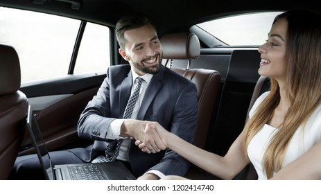 Handshake of business people in the back seat of a car