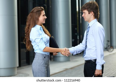 Handshake business smiling attractive young couple before the meeting, background - Shutterstock ID 112216940