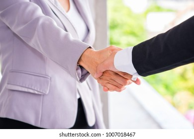 Handshake of businessman and businesswoman in the city congratulation and deal with partners.