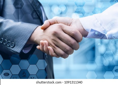 Handshake of a businessman and a doctor on blurred background.