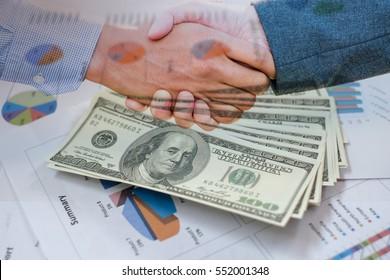 Handshake of businessmen on banknotes background