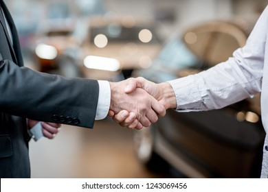 Handshake of a client and salesperson at the car showroom. Close-up vieww