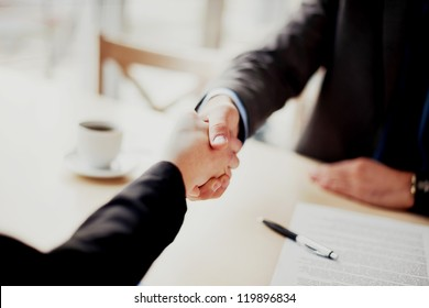 Handshake closeup of businesswoman and businessman.