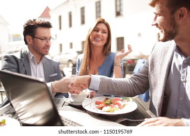 handshake colleagues at a table in a street cafe