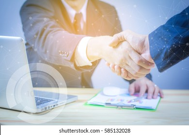 Handshake concept.two businessman shaking hands standing at the working place,laptop and digital tablet and graph financial with social network diagram and man working in the background