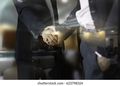 Handshake concept.two businessman shaking hands standing at the working place,and man working in the background