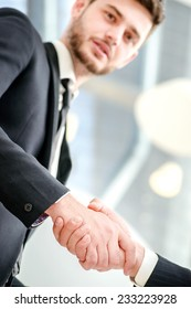 handshake deal. Two successful businessman standing in the restaurant and drink coffee while shaking hands with each other close-up view of hands