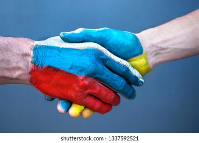 Handshake with the drawing of a flag of Ukraine and Russia