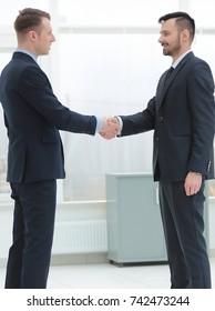 handshake financial partners in the corridor of the office