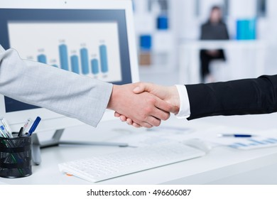 Handshake in gesture of agreement, with a blurry screen in the background